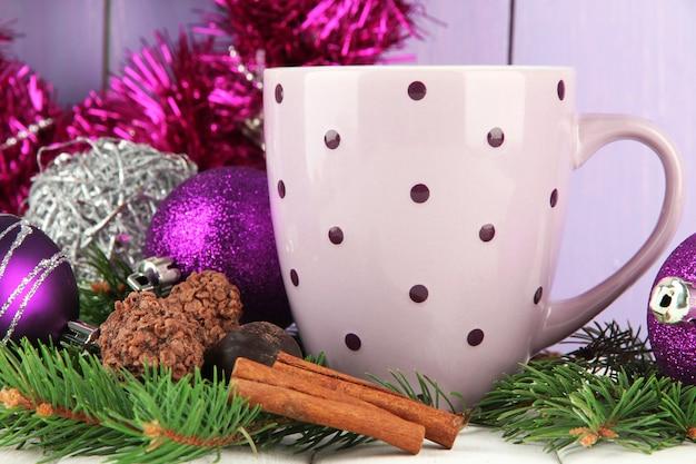 Kubek gorącego kakao z czekoladkami i ozdobami świątecznymi na stole na drewnianym tle