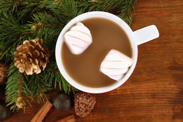 Kubek gorącego kakao z czekoladkami na drewnianym stole