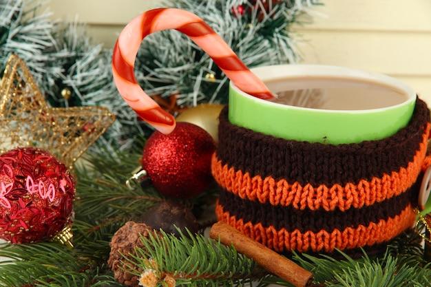 Kubek gorącego kakao z dekoracjami świątecznymi na stole na drewnianym tle