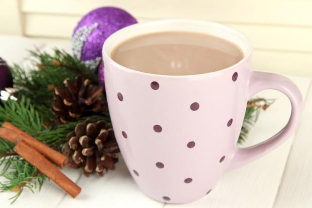 Kubek gorącego kakao z guzkami i ozdobami świątecznymi na stole na drewnianym tle
