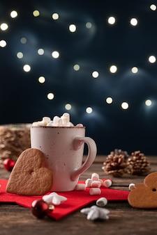 Kubek gorącego kakao z maleńkimi piankami w świątecznym otoczeniu świątecznym