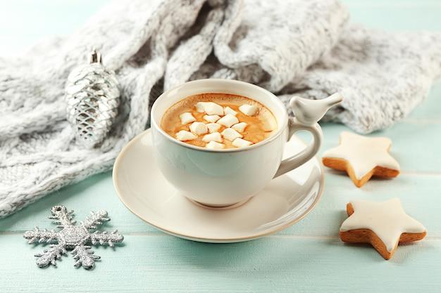 Kubek gorącego kakao z pianką, ciasteczkami i ciepłym szalikiem na niebieskim stole