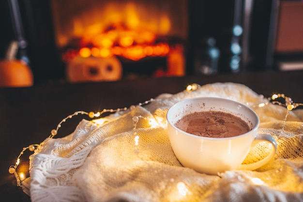 Kubek gorącego napoju przed kominkiem. święta bożego narodzenia. biały kubek stojący przy kominku. przytulna, relaksująca magiczna atmosfera w domku.