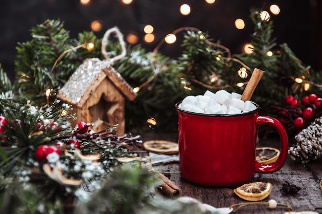 Kubek gorącego napoju z piankami i cynamonem wśród noworocznych dekoracji. piękna świąteczna dekoracja.