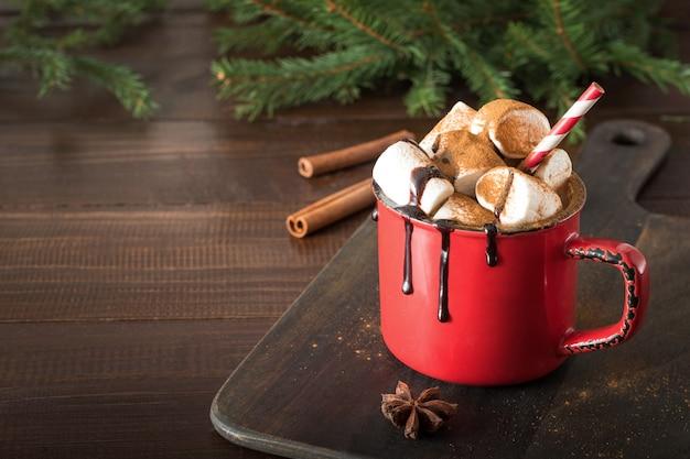 Kubek gorącej czekolady i kakao z pianki z gałęzi choinki na desce. święta bożego narodzenia.