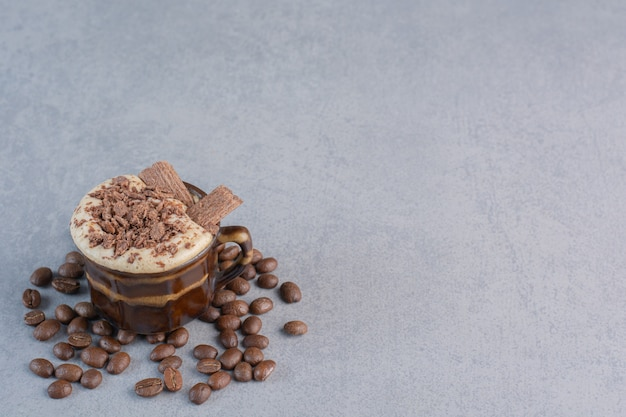 Kubek gorącej czekolady i ziaren kawy na kamieniu.