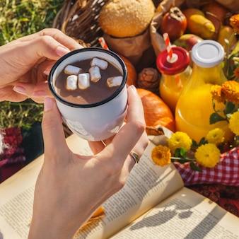 Kubek gorącej czekolady lub kakao z pianką w rękach kobiety