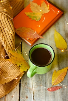 Kubek gorącej czekolady na drewnianym stole, martwa natura z książką i żółtymi liśćmi i girlandami