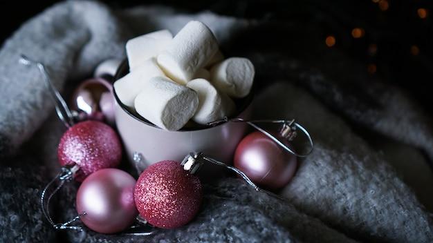 Kubek gorącej czekolady z pianką marshmallow na ciemnym tle, zimowy świąteczny gorący napój z różowymi bombkami - zdjęcie z bliska