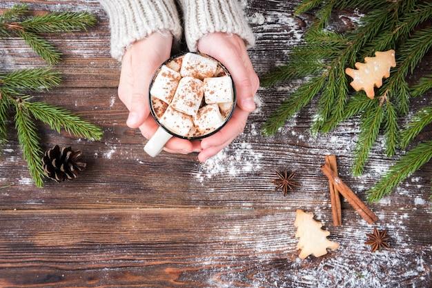 Kubek gorącej czekolady z pianką, przyprawami, świątecznymi ciasteczkami imbirowymi, gałęziami jodły i szyszkami na ciemnym tle drewnianych. skopiuj miejsce na tekst. świąteczna tapeta, karta.