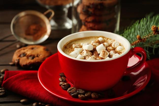 Kubek gorącej czekolady z piankami, gałąź jodły na drewnianym stole