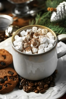 Kubek gorącej czekolady z piankami marshmallow, gałąź jodły na drewnianej powierzchni