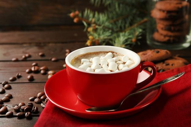 Kubek gorącej czekolady z piankami marshmallow, gałąź jodły na drewnianym tle