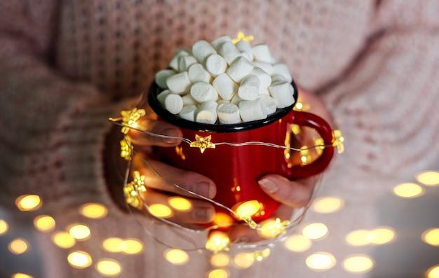 Kubek gorącej czekolady z piankami w rękach z lampkami choinkowymi