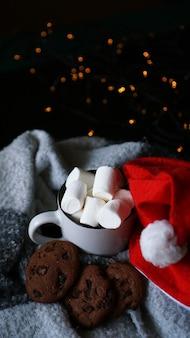 Kubek gorącej czekolady z świątecznym kapeluszem, pianką marshmallow i czekoladowymi ciasteczkami. duch świąt, gorący zimowy napój. selektywne ustawianie ostrości - zdjęcie pionowe