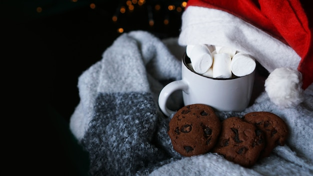 Kubek gorącej czekolady z świątecznym kapeluszem, pianką marshmallow i czekoladowymi ciasteczkami. duch świąt, gorący zimowy napój