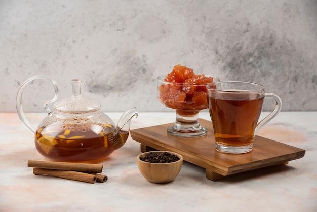 Kubek gorącej herbaty, czajnik i słodki dżem z pigwy na desce.