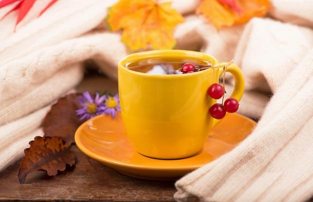 Kubek gorącej herbaty i liści jesienią, na brązowym tle