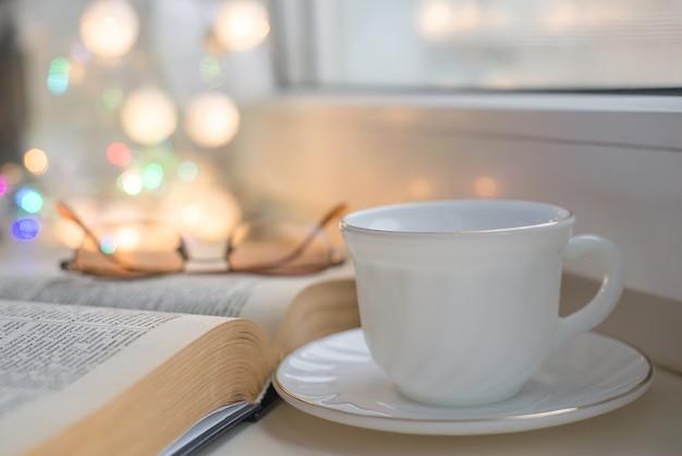 Kubek gorącej herbaty i otwarta książka na biurku