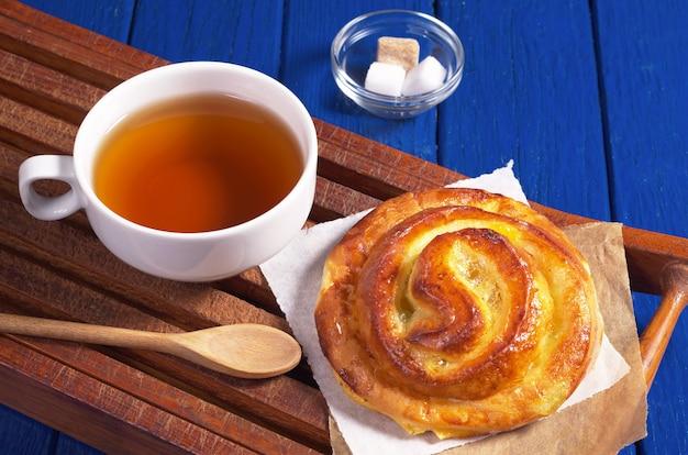 Kubek gorącej herbaty i słodka bułka z dżemem na niebieskim drewnianym stole