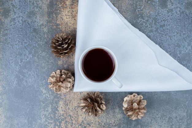 Kubek gorącej herbaty i szyszki na marmurowym stole. wysokiej jakości zdjęcie