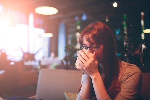 Kubek gorącej herbaty rękami kobiety. piękna kobieta z filiżanką kawy w restauracji