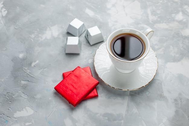 Kubek gorącej herbaty w białej filiżance na szklanym talerzu ze srebrnym opakowaniem cukierki czekoladowe na lekkim biurku, napój herbaciany słodkie czekoladowe ciasteczko