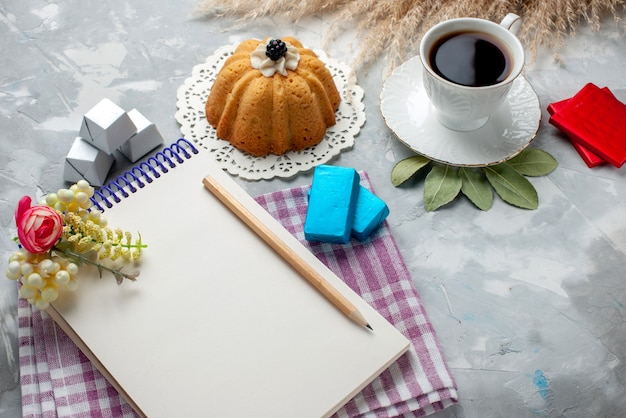 Kubek gorącej herbaty w środku biały kubek z ciastem notatnik czekoladki na lekkim biurku, słodki cukierek czekoladowy herbaty