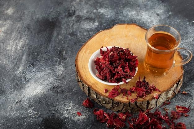 Kubek gorącej herbaty z suszonymi czerwonymi kwiatami na drewnianym kawałku.