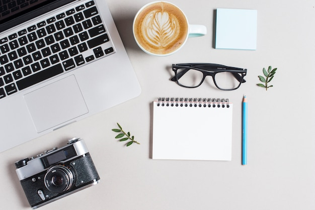 Kubek gorącej kawy cappuccino latte art; laptop i kamera z stationeries na białym tle