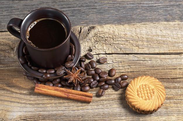 Kubek gorącej kawy i ciasteczka na starym drewnianym stole