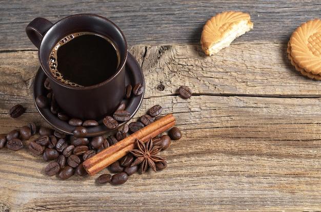 Kubek gorącej kawy i ciastek z kremowym nadzieniem na starym drewnianym tle