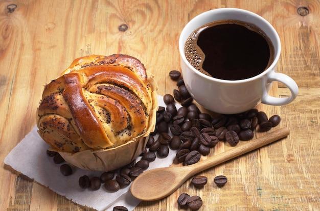 Kubek gorącej kawy i domowe wypieki z makiem na starym drewnianym stole