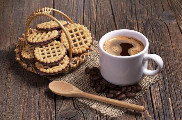 Kubek gorącej kawy i okrągłe ciasteczka w koszu z czekoladą na starym drewnianym stole