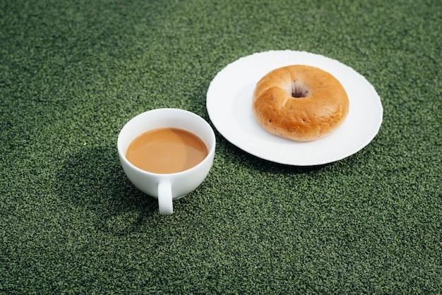 Kubek gorącej kawy i pączka w zimny poranek, na zielonej trawie z rosą w tle
