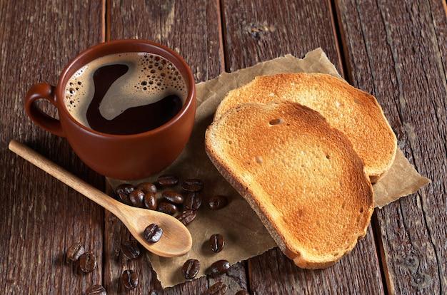 Kubek gorącej kawy i pieczony biały chleb na starym drewnianym stole