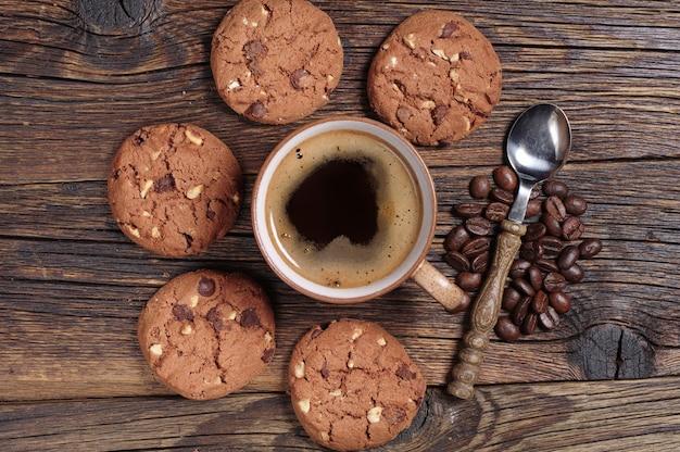 Kubek gorącej kawy i pyszne czekoladowe ciasteczka na starym drewnianym stole, widok z góry