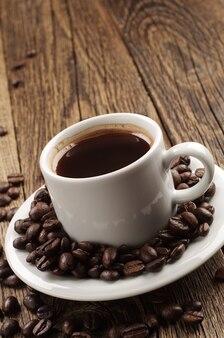 Kubek gorącej kawy i ziaren kawy na starym drewnianym stole