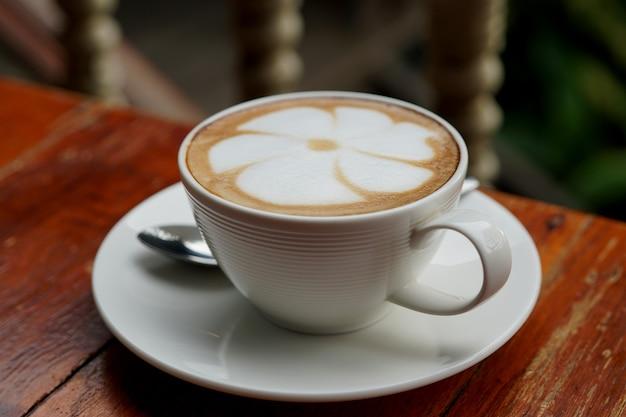 Kubek gorącej kawy latte art na drewnianym stole