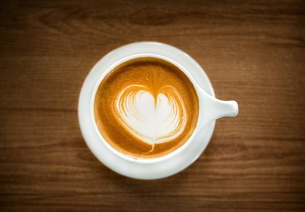 Kubek gorącej kawy latte na drewnianym stole. widok z góry