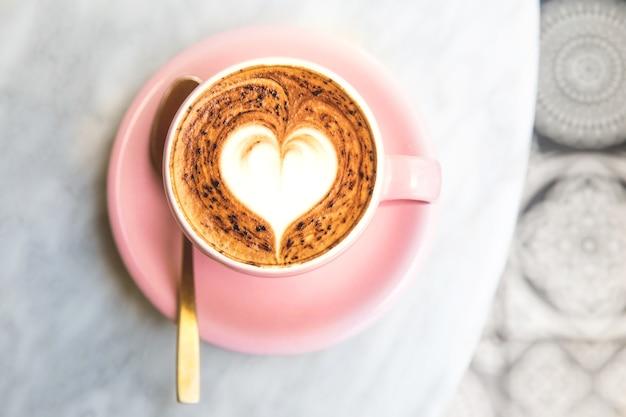 Kubek gorącej kawy latte na marmurowym tle stołu z podłogą artystyczną
