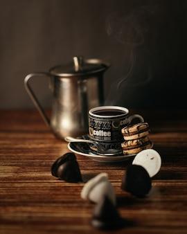 Kubek gorącej kawy z ciasteczkami na stole pod lampkami - idealny do konceptów napojów