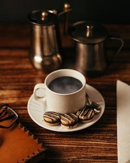 Kubek gorącej kawy z ciasteczkami na stole pod światłami