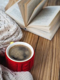 Kubek gorącej kawy z ciepłym zimowym swetrem i książką na stole. kompozycja zimowa
