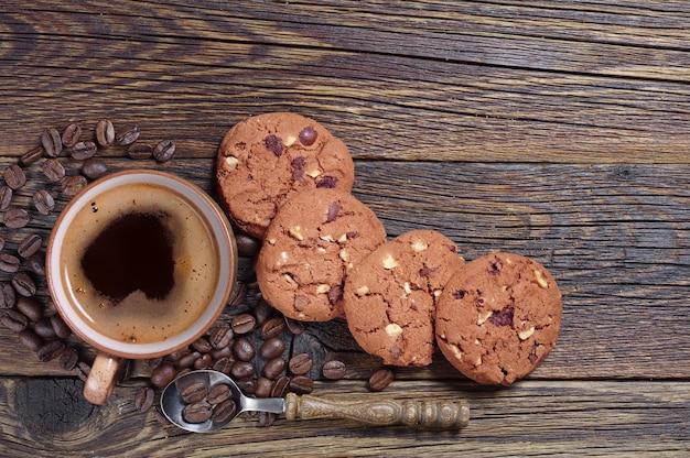 Kubek gorącej kawy z czekoladowymi ciasteczkami na starym drewnianym tle, widok z góry