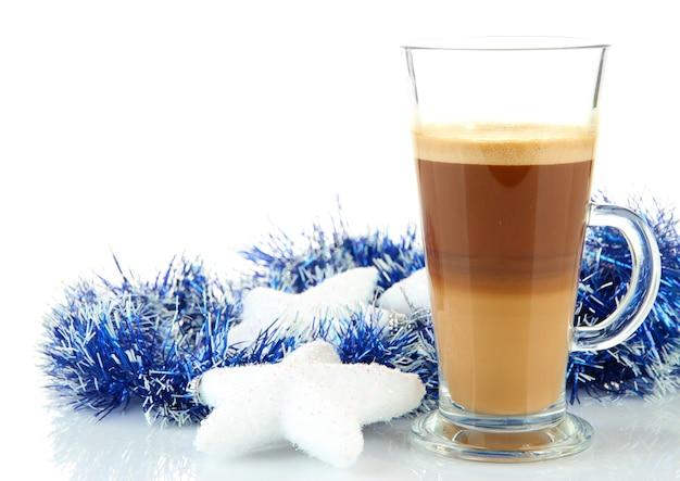 Kubek gorącej kawy z dekoracjami świątecznymi na białym tle