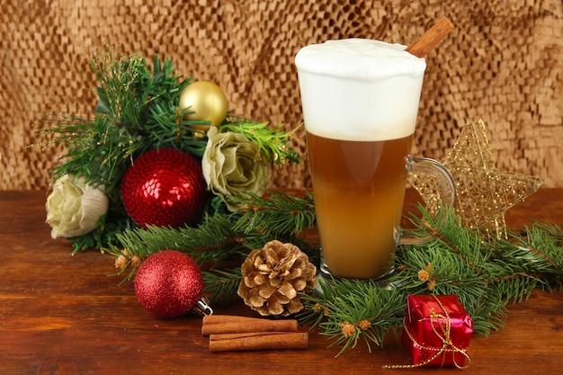 Kubek gorącej kawy z dekoracjami świątecznymi na stole na brązowym tle