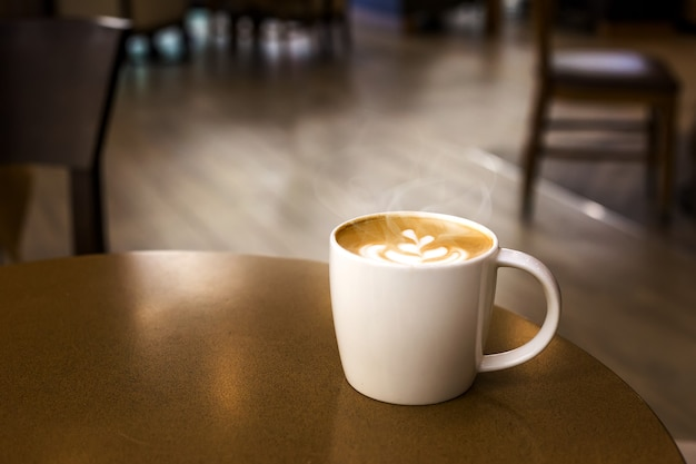 Kubek gorącej kawy z dymem na drewnianym stole w pustej kawiarni