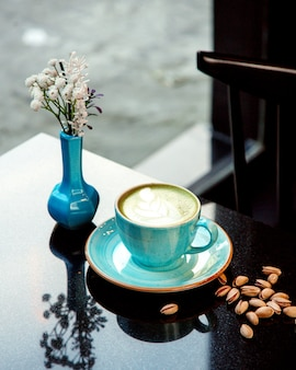 Kubek gorącej kawy z pianką i pistacjami