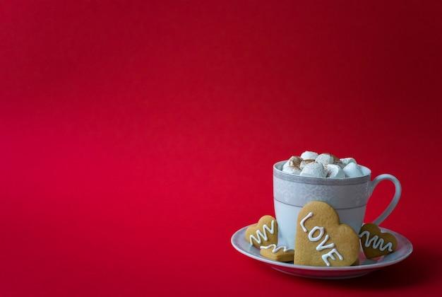 Kubek gorącej kawy z ptasie mleczko i ciasteczka serca z miłosnymi słowami. walentynki rano